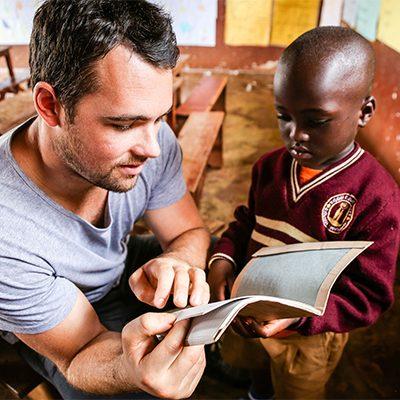 Blanke man leest Ugandese jongen voor uit boek