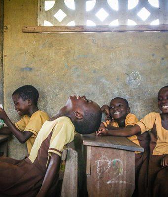 Lachende kinderen in een klaslokaal in Uganda
