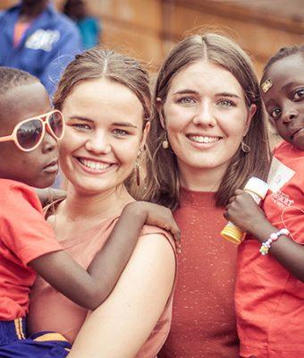 Twee vrouwen lachen met kindjes op hun arm