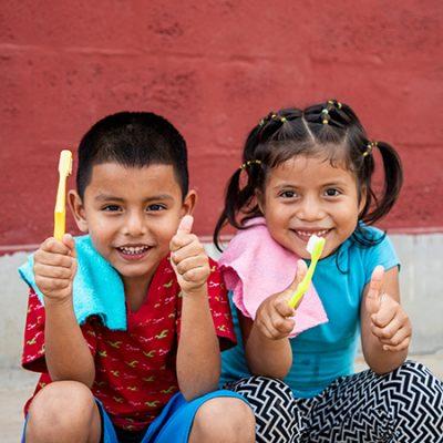 twee sponsorkinderen met tandenborstel steken hun duim op