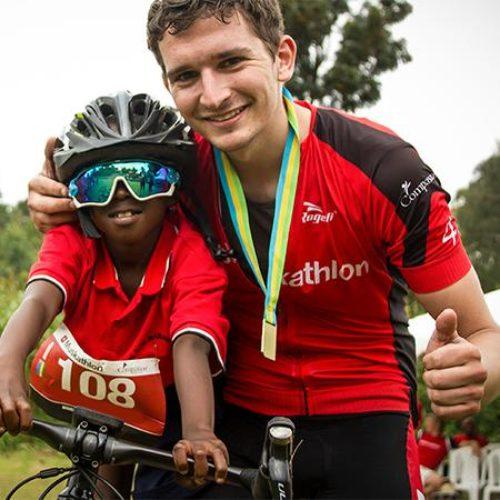 Deelnemer van de Muskathlon poseert met Afrikaans jongetje die met zijn zonnebril op op zijn mountainbike zit