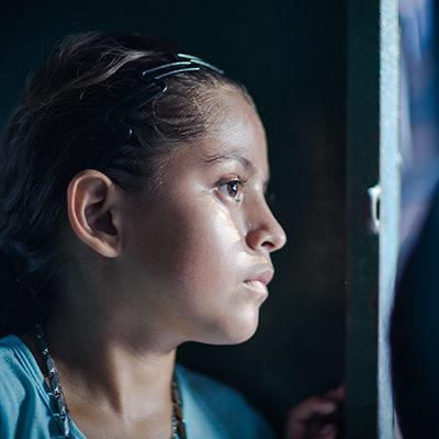 Meisje uit Honduras kijkt uit het raam