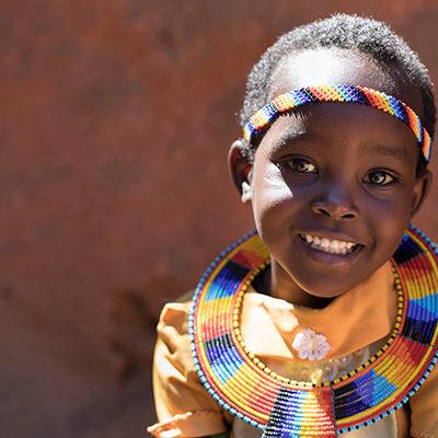 Afrikaans meisje in traditionele kleding lacht in de camera