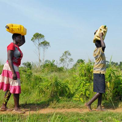 twee afrikaanse tieners lopen met waterflessen op hun hoofd