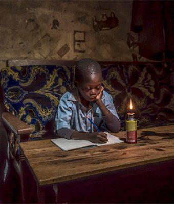 JOngen zit aan tafel te lezen bij kaarslicht