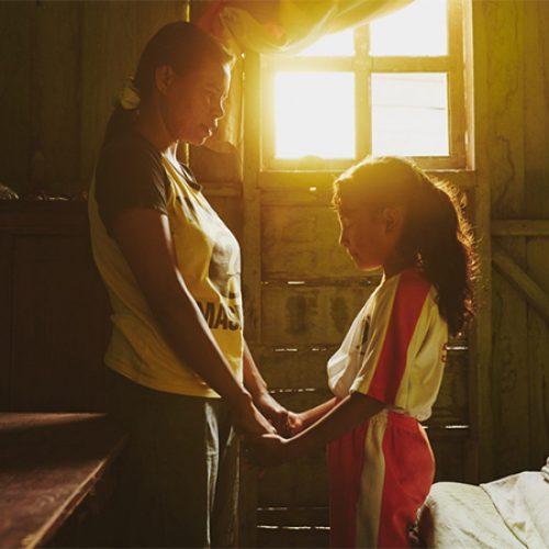 Volwassene en kind bidden samen