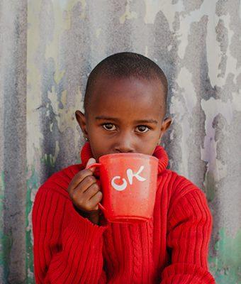 Keniaanse jongen drinkt uit een beker