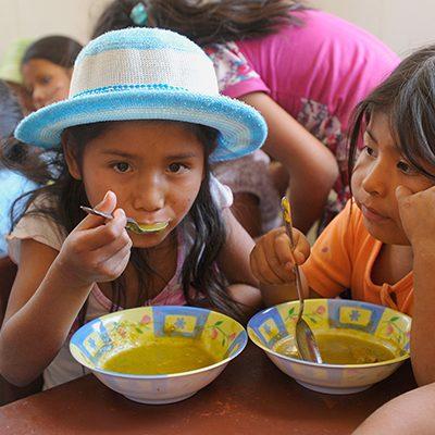 Boliviaans meisje eet uit een kom