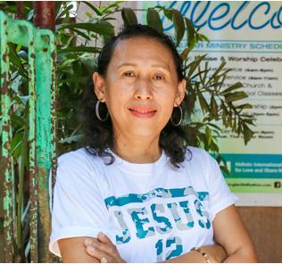 Filipijnse vrouw in wit shirt met armen over elkaar