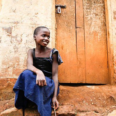 Ugandees meisje voor haar huis