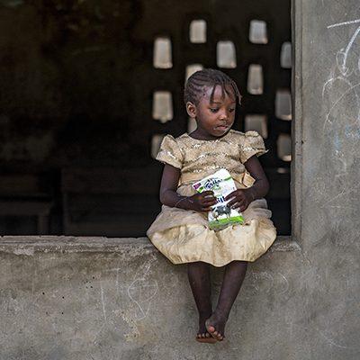 Keniaans meisje zit op een muur