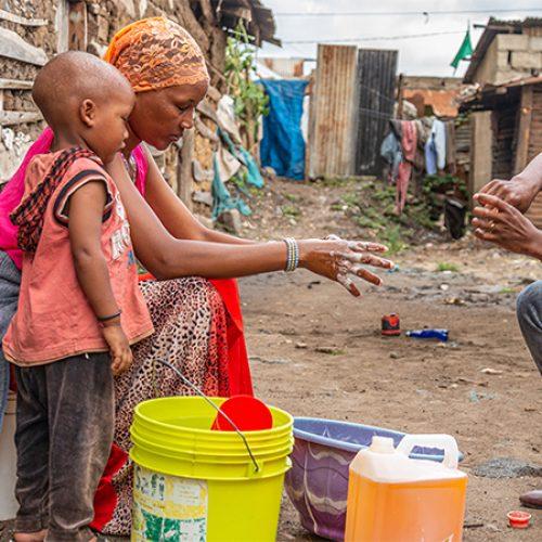 Tanzaniaanse moeder en kind wassen handen