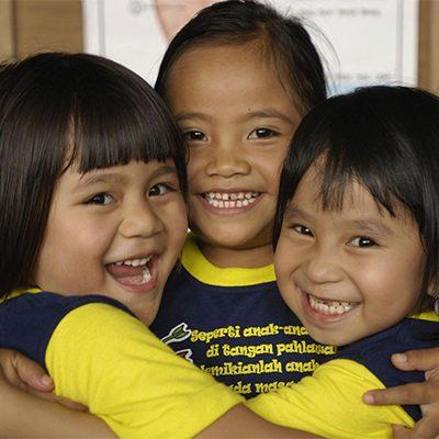 drie indonesische meisjes knuffelen elkaar