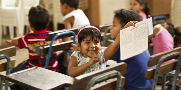 Meisje zit achterstevoren in de klas en houdt blij een brief omhoog