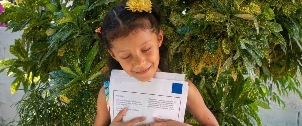 Meisje met gele bloem in haar haar houd haar brief dicht tegen zich aangedrukt