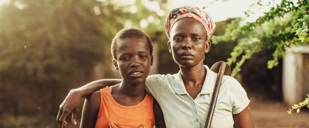 Moeder met lichtblauw poloshirt en werktuig over haar schouder slaat arm om meisje in oranje hemd.
