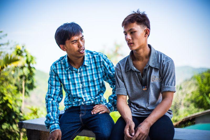 Man met blauwe ruitjesbloes zit met een tiener in grijze polo op een muurtje