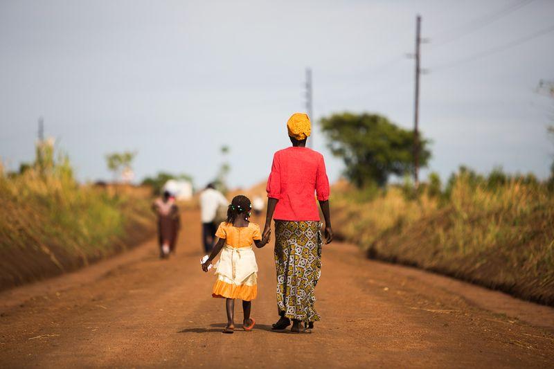 Vrouw met oranje hoofddoek, rode bloes en wit/gele rok loopt hand in hand met meisje in oranje jurk over rode zandweg in Uganda
