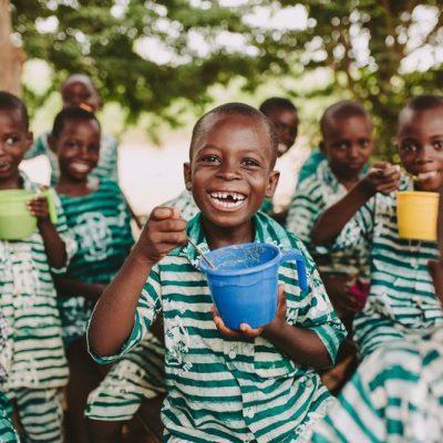 Lacehden groep kinderen in groen wit gestreept schooluniform met bakjes pap