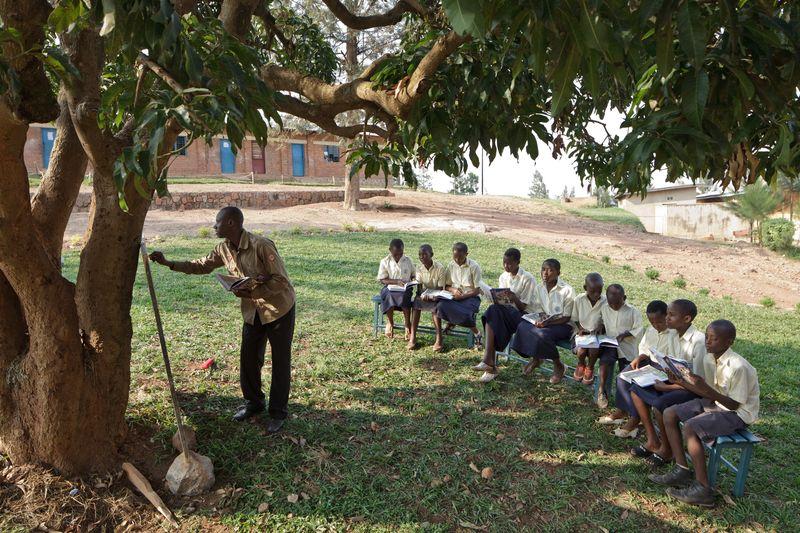 Tien kinderen in een halve kring onder een boom waar de leraar iets op een bord schrijft