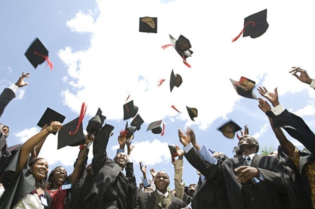 Jongeren in graduation-jurk gooien hun hoedjes in de lucht