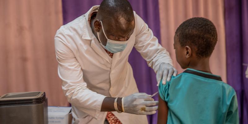 Jongen in blauw shirt krijgt vaccinatie van arts in witte jas met mondkapje